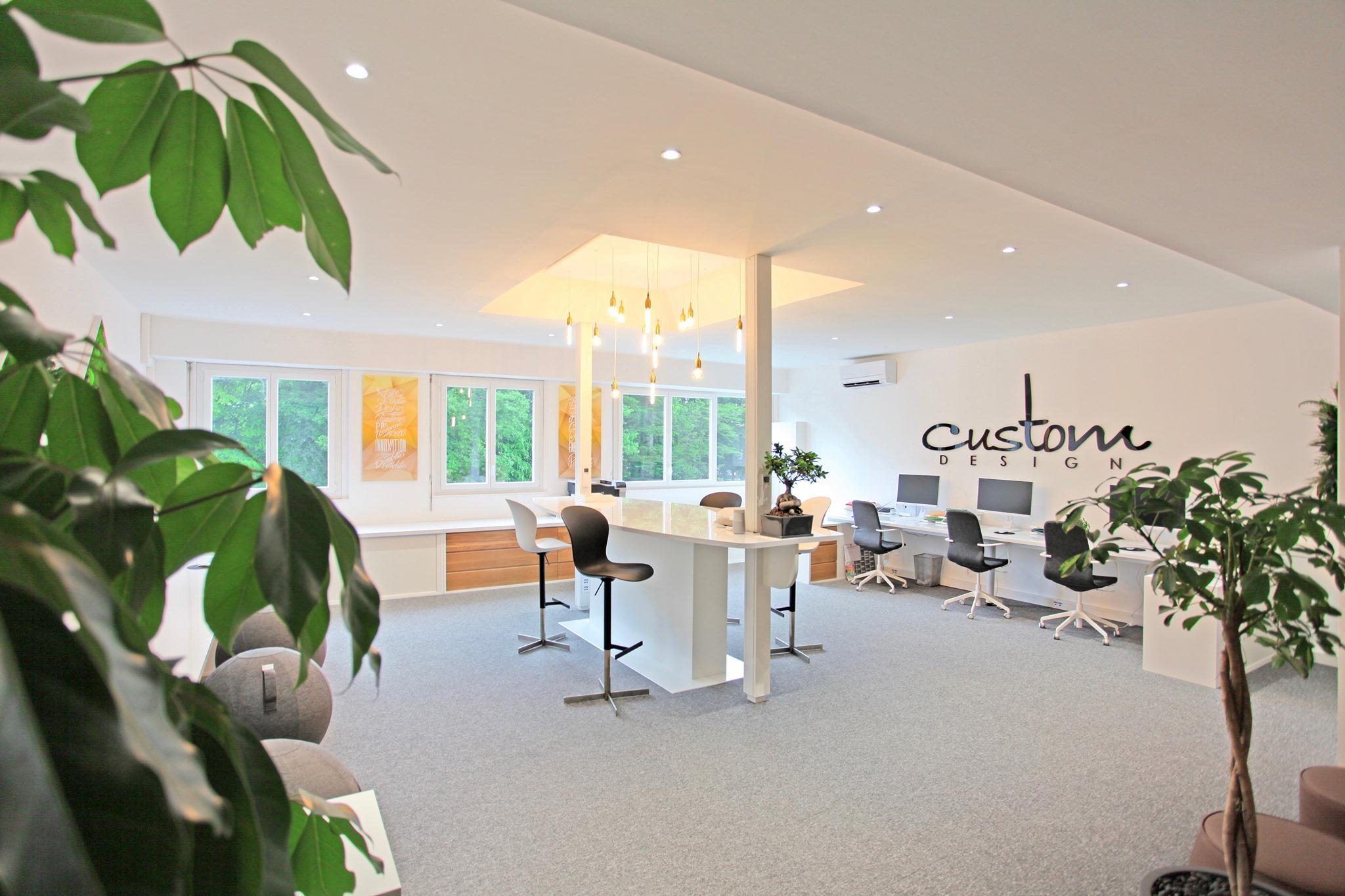 Photo de l'open-space. L'espace dispose de six postes de travail de type bureau et d'un ilot central plus haut autour duquel sont disposés des tabourets haut.